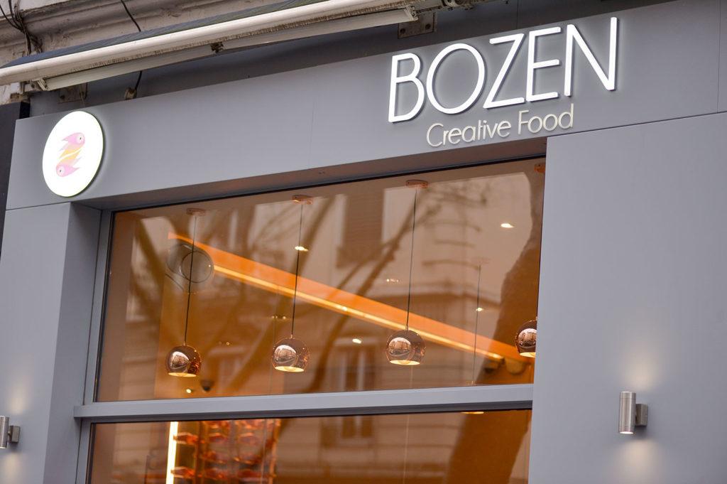 Devanture vitrée en menuiserie aluminium du restaurant Bozen avec enseigne lumineuse