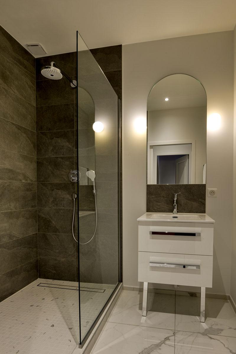 Agencement d'une salle de bain avec un pare douche en verre et un miroir par la Miroiterie du Rhône